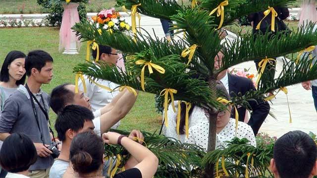 来宾向逝者献花并将黄丝带系上树枝祈福640x360